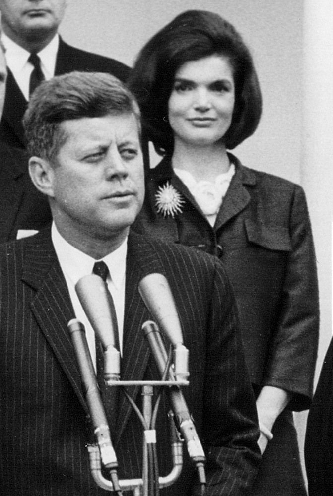 President John F. Kennedy speaks during a press conference as First Lady Jackie Kennedy looks on April 9, 1963 at the White House.