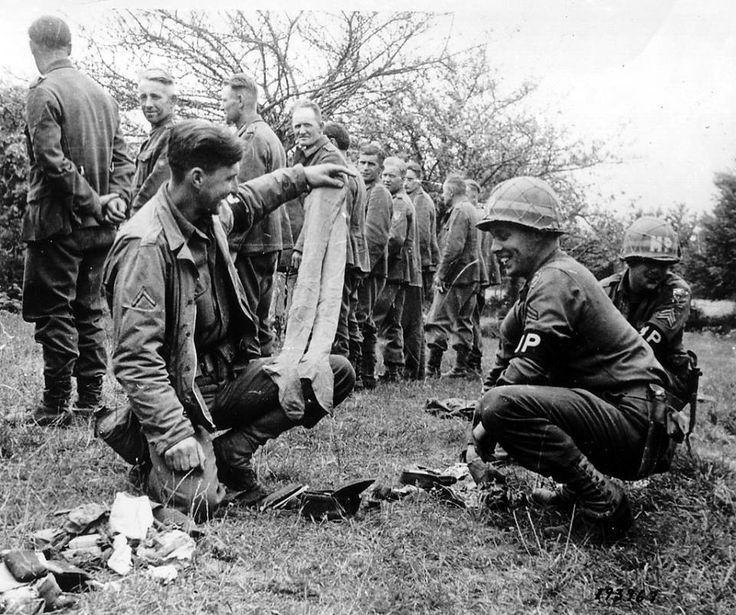 Camp de prisonniers La Motterie à La Glacerie (7 km de Cherbourg), 25 juin 1944. Des prisonniers allemands sont fouillés. Tandis qu'ils sont alignés, derrière eux, un Pfc montre une paire de bas à un Cpl M.P.Platoon de la 79th US ID. Il s'agit du Cpl Joseph DANNER de Harford, Connecticut et du Sgt Bruno SKOCNANSKI de Newark. N-J.