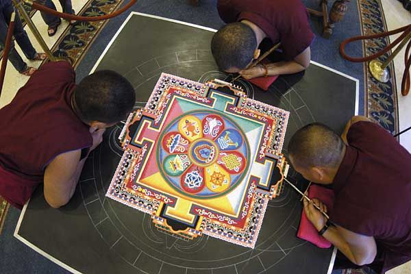 """Tibetan Monks of the Drepung Loseling Monastery creating a mandala sand painting at the Memorial Union's Main Lounge. Mandala is a Sanskrit word meaning cosmogram or world in harmony. When finished, it is destroyed to symbolize the impermanence of all that exists."" Photo by Jeff Miller, 2003, caption from link, U of Wisconsin-Madison"