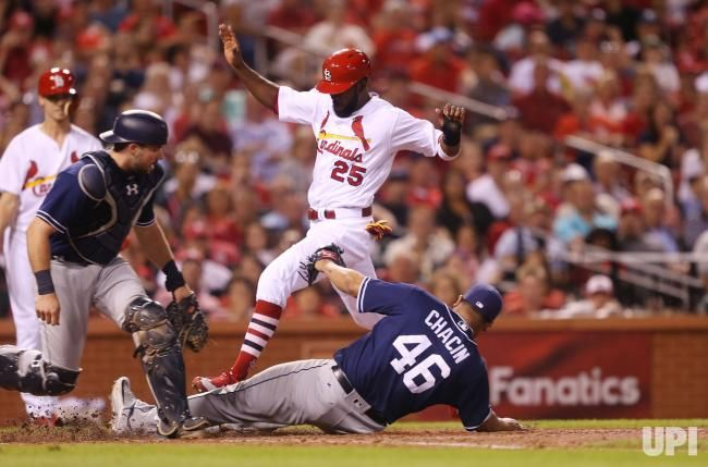St. Louis Cardinals Dexter Fowler jumps over San Diego Padres starting pitcher Jhoulys Chacin to score on a wild pitch in the fifth inning…