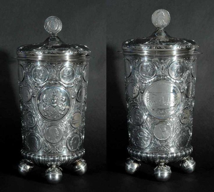 """Münzpokal """"L. Bertsch"""" 800 Silber, 2155 g, reich relief. Dekor mit preußischem Adelswappen, Wandung und Deckel mit eingelegten Münzen/Medaillen, 4 relief. Kugelfüße, Deckel mit Münze als Knauf, H= 37 cm, um 1900"""