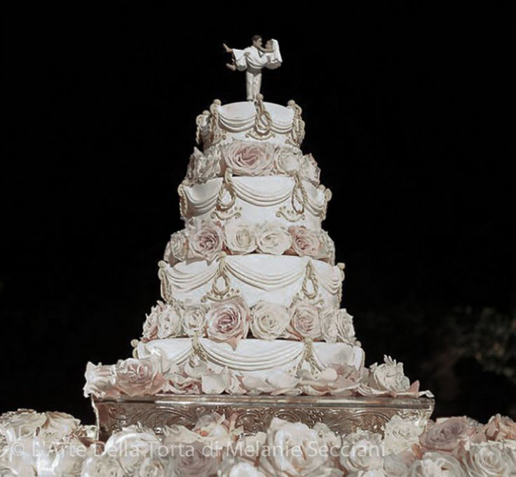Tuscany Wedding cake by L'Arte Della Torta di Melanie Secciani in Florence, Italy. At La Suveria near Siena, Italy – a 4 tier wedding cake in ivory and gold. Cake was tiered floating on beds of roses adorned with 24 pieces of sugar ribbon swag, edible tassels, and hand piped details. The cake inside was lemoncello dream: vanilla cake with wild berry coulis and lemoncello cream. As pictured serves 218.