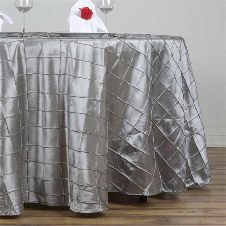 """Silver Pintuck Tablecloths 132"""" Round - Pintuck is actually a fold of fabric that is stitched intricately to hold it in a place, very much like a pleat. These lovely pleats impart a decorative effect to the fabric by fashioning a visual line at a chosen point. They effortlessly bridge vintage and contemporary styles to create a majestic new classic look. If you do not want your celebration to blend in with other weddings, birthdays, and anniversaries, try our premium quality pintuck…"""