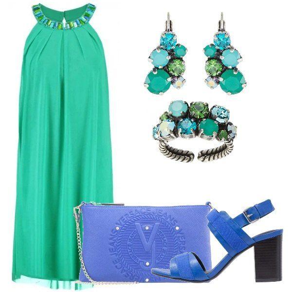 Vestito senza maniche verde, scollo tondo con pietre girocollo, sandali blu elettrico dal tacco comodo, borsetta Versace Jeans con zip e catenella, anello e orecchini con pietre verdi e azzurre.