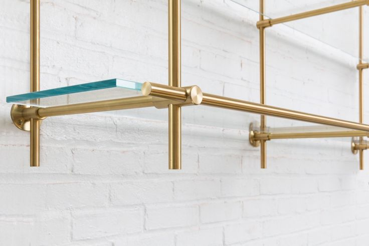 Details of our Collector's Shelving System. Brass finishing and glass shelves creates a clean feel desired for any space. Seen here in a kitchen.