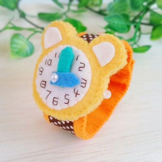 フェルトで作ったおもちゃの腕時計です。時計部分は可愛いクマ型で、文字盤の数字は全てひとつひとつ手刺繍しています。長針と短針はお好きな位置へ動かす事ができます。ベルトの着脱はボタンで、三段階の長さ調節が可能です。お子様のごっこ遊びや普段のお洒落、ディスプレイなどに。またプレゼントにもおすすめです。●カラー:時計部分…山吹色   ベルト…茶色のドット柄●サイズ:ベルト長さ 18cm●素材:フェルト、ビーズ、ファブリックテープ、ボンド●注意事項※小さなパーツや一部にボンドを使用していますので、お子様が口に入れたりしないよう充分にご注意ください。※時計の針は同じ方向に回し過ぎると、縫い止めている糸が切れたり、フェルトが傷んで破損の原因となりますので、同じ方向に一周以上回さないようにお願い致します。※出来るだけ丈夫に作ってはいますが、フェルトの性質上、またハンドメイド品のため市販品のような強度はありません。優しくお取り扱い頂けますようお願い致します。●制作者: gokko…