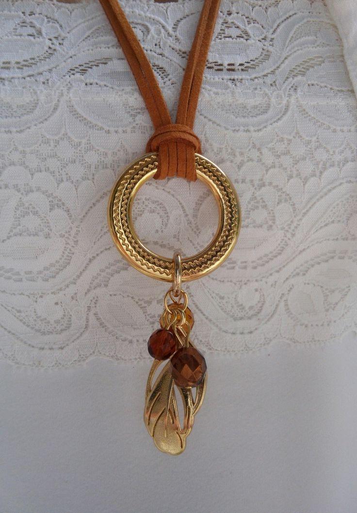 Colar de camurça na cor ocre alaranjado com argola dourada e pingentes de pena e cristais marrom cafe, marrom dourado e amarelo. Fecho anzol dourado.