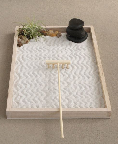 Small desktop Zen garden for meditation comes with relaxing air plant and stacked stone cairn.