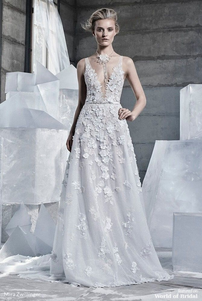 8e45a21d3ff6 Mira Zwillinger 2019 A-line bridal gown. V-neck A-line gown over sparkle  mesh tulle with 3D beaded floral appliquè. Matching long beaded neck  accessory.