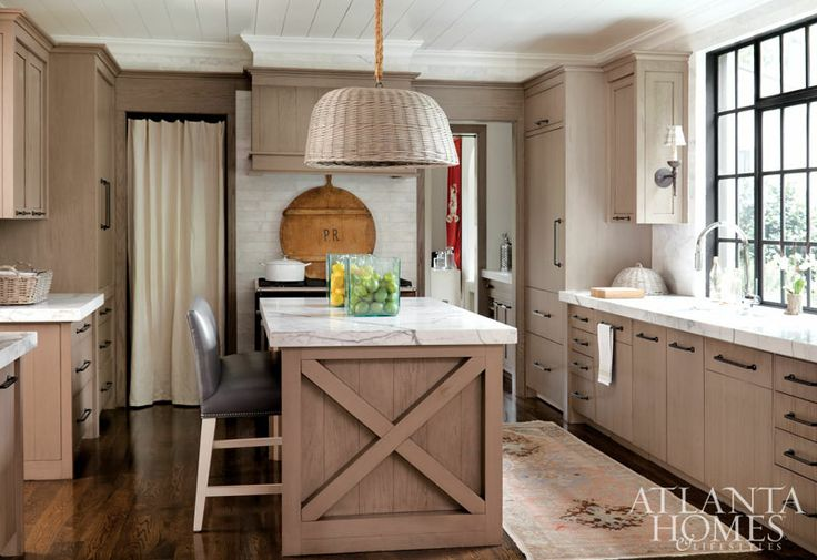 calcutta gold marble counters + custom wood cabinets + curtained pantry in kitchen design by Betty Burgess via Atlanta Homes