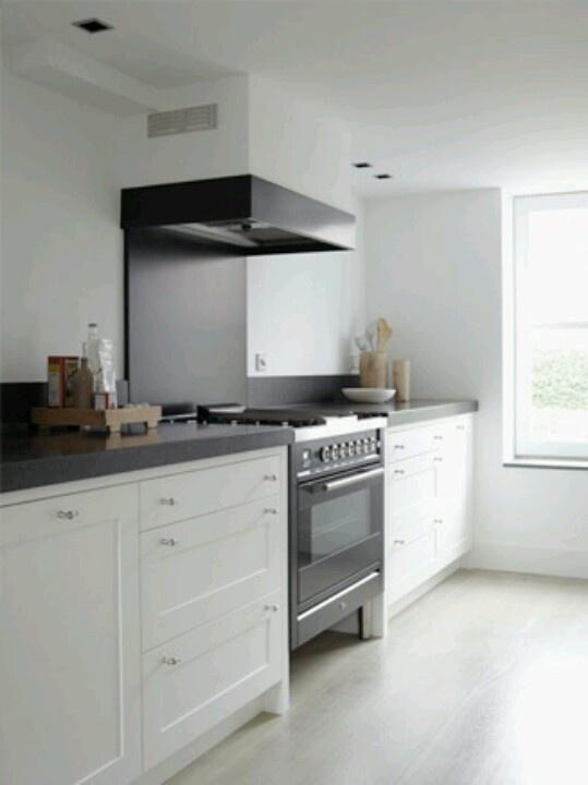 Moderne keuken met donker blad en witte kastjes. grote oven (aparte unit) opstaand randje van ongeveer 10 cm tegen de keukenwand.