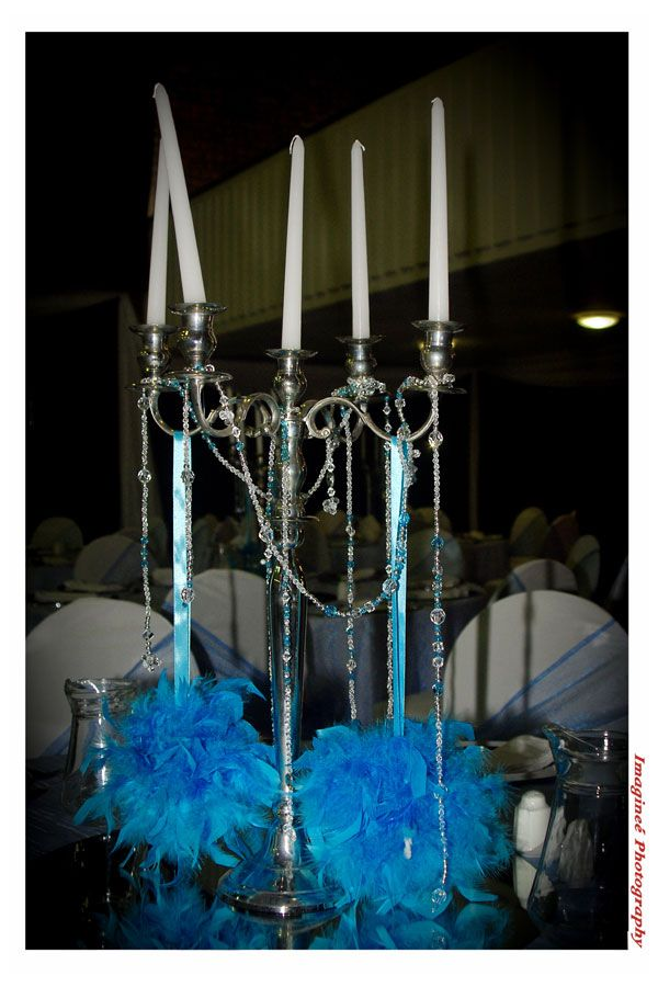 Candelabra with blue feather balls suspended and draped with strands of beads www.iceevents.co.za