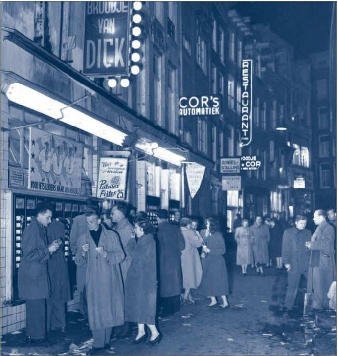 Een stadsstraat omstreeks 1950 met verschillende gelegenheden voor het gebruiken van 'een snelle hap' buitenshuis: broodjeszaken, een klein restaurant, automatieken en patates-friteswinkeltjes, die de authenticiteit van hun waar benadrukken door de herkomst ervan aan te geven: Fritures d'Anvers. Uit: K. Ribbens, Verleden Tijd. Nederland tijdens de wederopbouw (Zaltbommel 1992).
