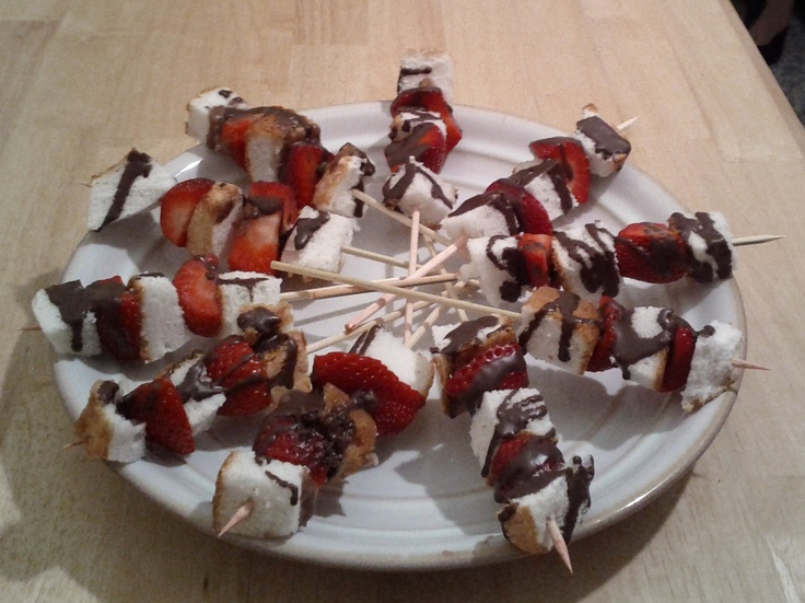 "Wood skewers, halved strawberries, Angel Food cake cut into small squares, and ""Magic Shell"" hardening chocolate"" drizzle"
