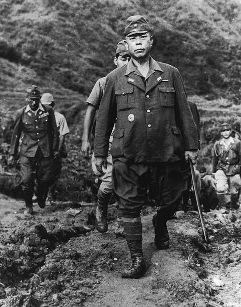 Japanese army general Tomoyuki Yamashita uses a cane while walking along a dirt road ahead of several soldiers Yamashita was known as the 'Tiger of...
