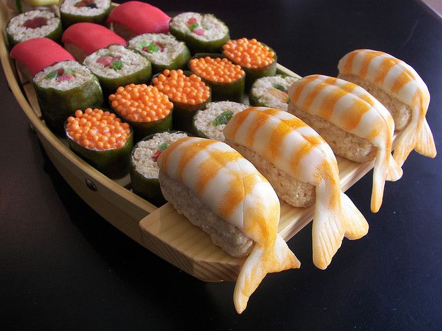 """Desert Sushi:)  The rice is rice krispie treats, the shrimp  is vanilla tootsie rolls that are handpainted  with food coloring, the seaweed is fruit  rollups, the tuna are airheads, and the guts  of the rolls are gummy worms, twizzlers and  other flavored tootsie rolls. Orange dots are large non-pareilles"""