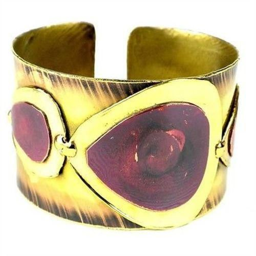 With teardrops of copper on polished brass, this brass cuff made by South African artisans catches and reflects light with each movement. The deep red color of the copper is achieved by applying high heat rather than paints or dyes.Bracelet dimensions: 40 mm wide x 7 inches long