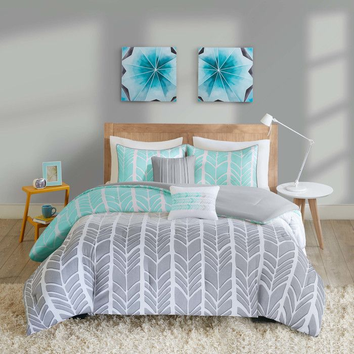 The Intelligent Design Nadia Comforter Set turns any bedroom into fun and inviting getaway. This stylish comforter features a grey and white chevron print broken up by white vertical stripes and a solid teal color that pops! Matching sham(s) with a teal flange pairs exceptionally well with the delightful chevron pattern, while two decorating pillows in coordinating colors help complete the look. Completely reversible, the comforter can flip to a solid grey, for a more neutral look. Made from…
