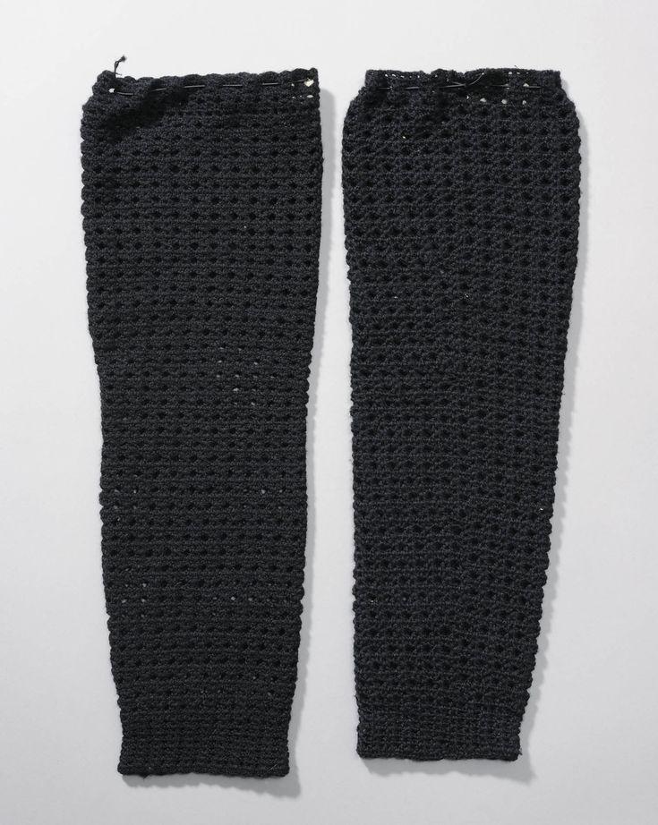 Een paar polsmoffen van zwarte wol, gehaakt in gaatjespatroon. #Arnemuiden