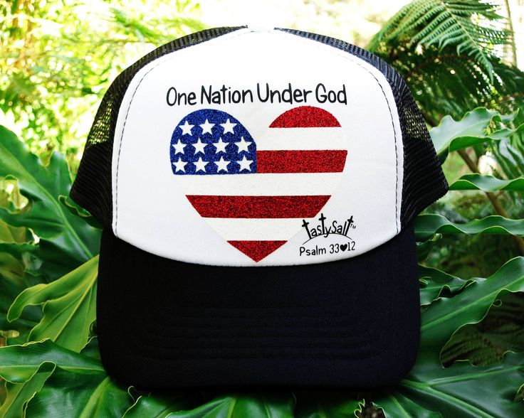 Black and white women's Christian mesh back trucker cap. Handmade, hand pressed heart shaped United States of America Flag with shimmering red and white stripes and glittery white stars on royal blue background design. Enjoy!