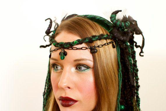 Deze donkere goddelozen schoonheid heeft lang zwart en donker groene opknoping van dreadlocks/garens. Iriserende echte pauwenveren, en diverse zwarte kralen glans in je haar. Een zwarte ketting met bengelende zwart/groen juwelen loopt over je voorhoofd, en hangt naar beneden aan beide zijden van de hoofdtooi. Hoorn-achtige dread krullen, en zwarte wol kroon deze schoonheid, met groene veren schieten. Deze hoofdtooi is gebouwd op een hoofdband, en is zeer licht. Een elastiek in de rug, die…