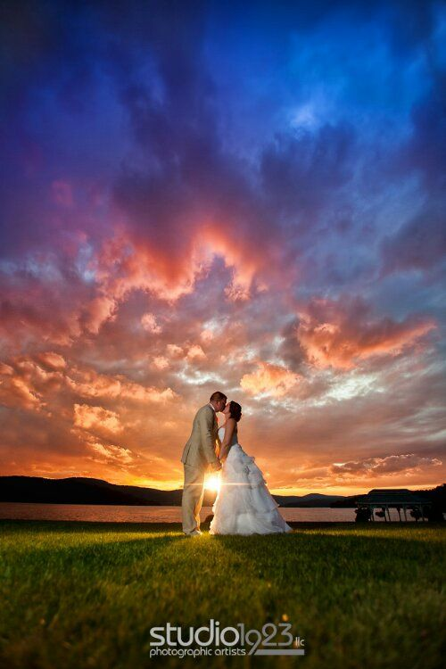 Sunset wedding photo. Couple kissing under the vividly colored sky.