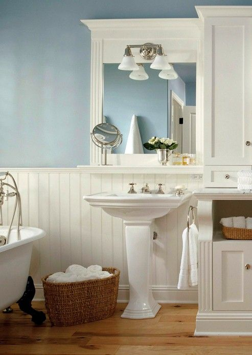 Crisp beaded-board wainscoting, graceful pedestal sinks, and a claw-foot tub create classic seaside style in this master bathroom. A palette of cloud white and ocean blue continues the theme. The wood floors add a sandy hue underfoot.  Twin pedestal sinks instead of a massive vanity lend to the spaciousness.  A claw-foot tub continues the theme of classic elegance.  Mirrors with ledges provide storage, as does a built-in armoire.  Displaying towels in baskets is a spa-like touch.