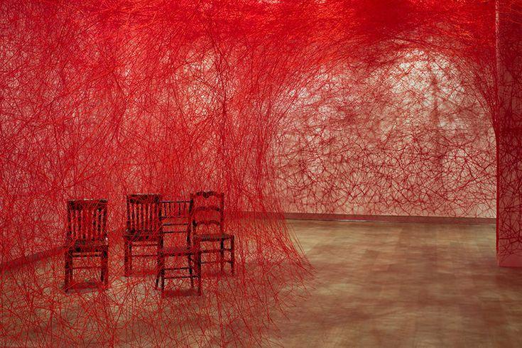 L?artista Chiharu Shiota tesse a mano un enorme bozzolo di fili rossi e sedie antiche