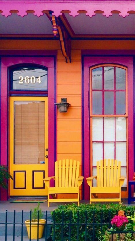 TETRADA- está fachada pintada con amarillo, naranja, morado fuerte y un arbusto verde crea una tetrada.
