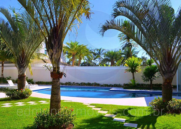O projeto de paisagismo e iluminação noturna faz com que a piscina pareça um oásis à noite, em meio às diferentes espécies de palmeiras e florzinhas rasteiras que foram espalhadas sobre o gramado e margeando o muro do terreno.