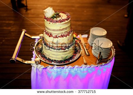 Multi-tiered wedding cake with cranberries and white rose on top, rolled out on trolley with knife and plates, illumination at banquet. Delicious, newlywed, celebration, party, evening, holidays.
