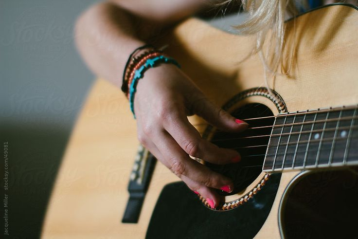 Teenage Girl with Bracelets and Painted Fingernails Playing a Guitar.