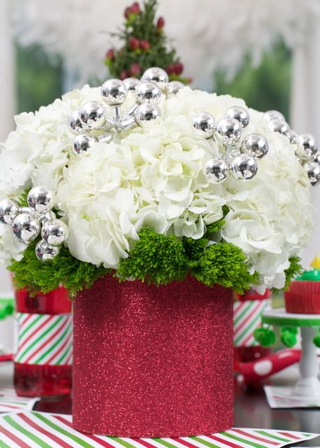 White flowers with greenery and silver bells in a red vase for Christmas decor. | Flair Designery