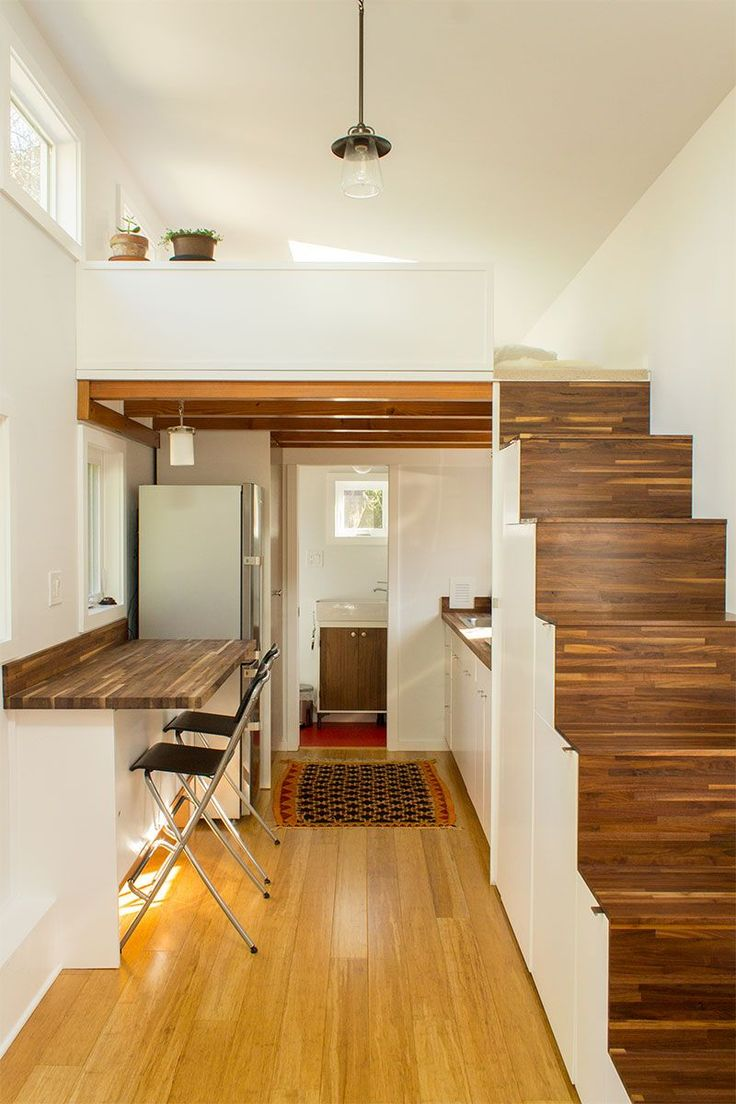 Stairs that double as storage in an open living and dining space in a tiny house. sm
