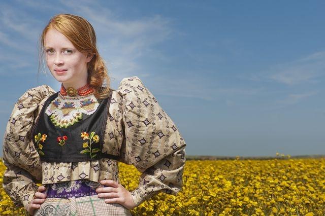 Het model is de 16-jarige Evelien uit Zoutelande. Ze draagt verschillende historische stukken uit onze modecollectie waaronder een schapenbout uit Schouwen en een Axels beukje. De foto is op Walcheren gemaakt door Anda van Riet en Karina Leijnse.