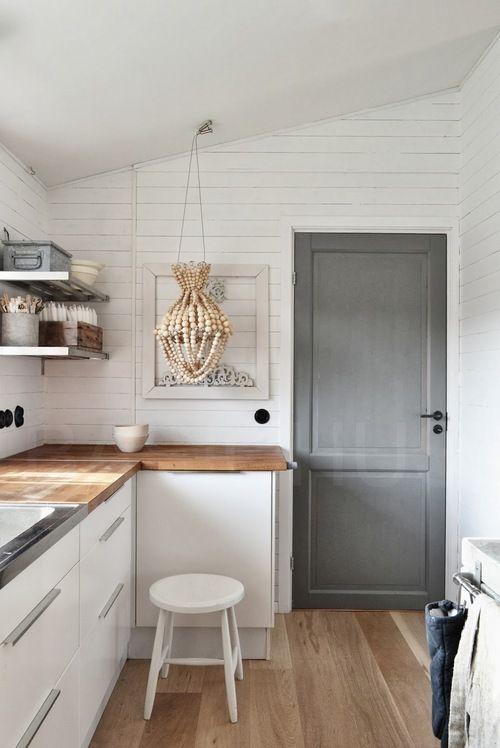 Grey door, honey countertops, white cupboards. Textured walls and floors. Black hardware.