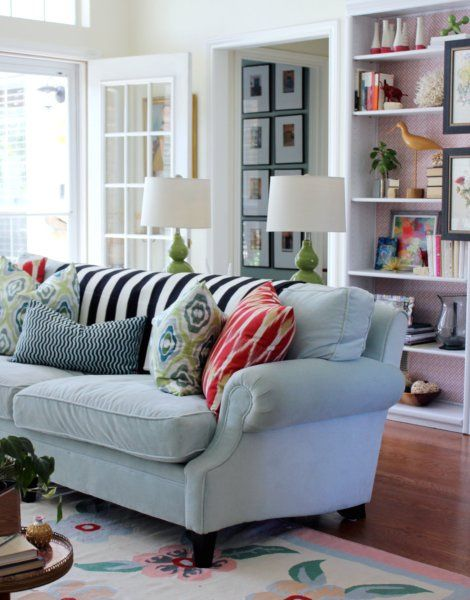 love the colors + patterns and styling of this living room. I'd replace the striped throw with a soft white, very pale green, light grey or blue one.