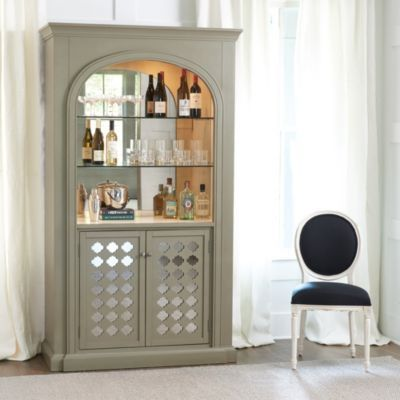 We designed the elegant Karidee Bar Cabinet with all the architectural detail and function of a built-in with the versatility of a furniture piece. Two adjustable glass shelves illuminate with two interior touch lights. Four pullout shelves below with removable racks hold up to 16 bottles of wine. Two deep slide-out shelves beneath handle the heavy stuff. Antiqued mirror in the back and behind the carved cabinets doors reflect light and sparkle.Karidee Bar Cabinet features:Gray finish with…