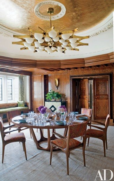 The dining room's brass-and-frosted-glass light fixture is a 1964 design by Gio Ponti, the oak-and-bronze table is by Hervé Van der Straeten from Ralph Pucci International, and the vintage chairs are by Carlo di Carli and are covered in a Christopher Hyland cotton | archdigest.com