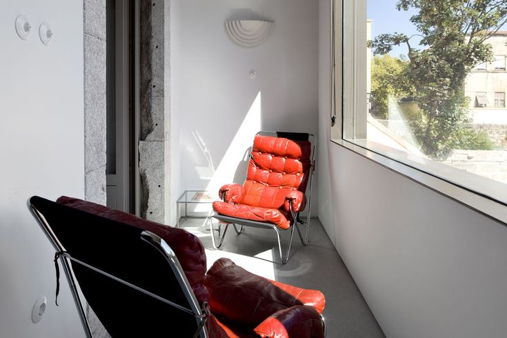 Red leather vintage chairs on a striking building with concrete suites and a mix of designer and period furniture. Casa do Conto   Porto  
