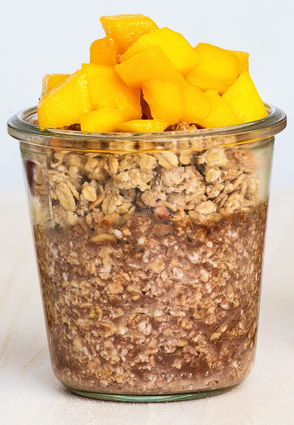 """Overnight Oats """"Schoko-Mango-Knusper"""": Haferflocken in ein Schraubglas oder eine Schüssel füllen. Die gewünschte Flüssigkeit im Verhältnis 1:1 oder 1:2 unterrühren. Das Gefäß verschließen und über Nacht in den Kühlschrank stellen. Am nächsten Morgen leckere Toppings hinzufügen, umrühren und genießen! Das Rezept für die Variation """"Schoko-Mango-Knusper"""" gibt es in der aktuellen Ausgabe der ALDI inspiriert unter www.aldi-sued.de/aldi-inspiriert."""