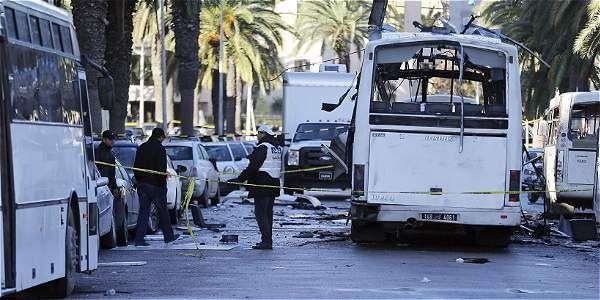 Policías forenses tunecinos inspeccionan los restos de un autobús tras el atentado contra varios guardias presidenciales que viajaban en el vehículo, en Túnez (Túnez).