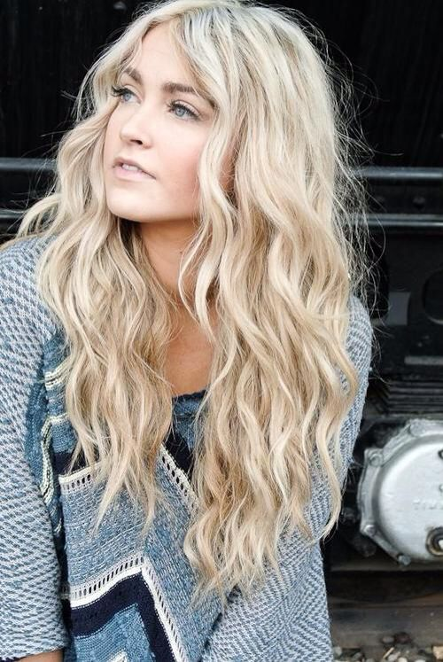 Long light blonde hair, dark eyebrows, beachy waves.
