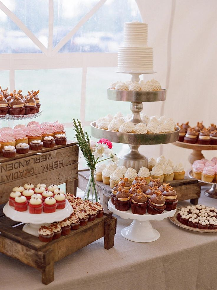Guests won't know what treat to choose with this amazing dessert table made up of a wedding cake and an assortment of small and large cupcakes.