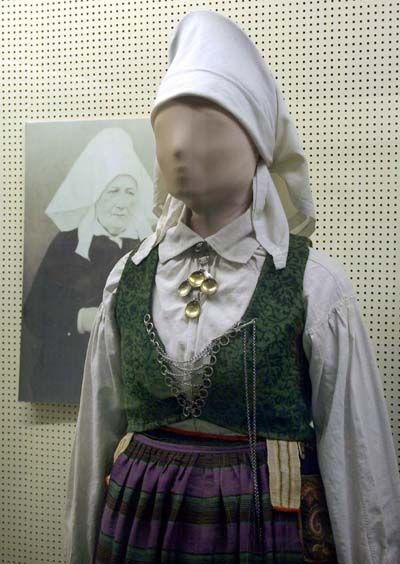 Den gifte kvinnens hodeplagg, med vase og skautet knyttet. I skjoeten sitter sølvknapper, hjertesølje med løv. I uppluten, vesten, som er av ulldamask, ser vi snørekjede med spyd.