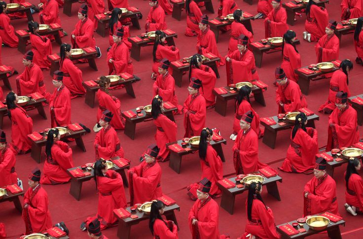 Newlyweds dressed in Han-dynasty costumes bow to each other during a traditional group wedding ceremony in Xi'an, Shaanxi, China.