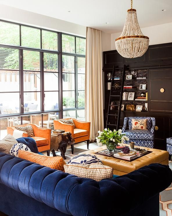 Beautifully furnished blue and orange contemporary living room boasts a blue velvet chesterfield sofa topped with orange, white, and blue pillows placed facing an orange leather ottoman coffee table positioned beneath a white beaded chandelier.