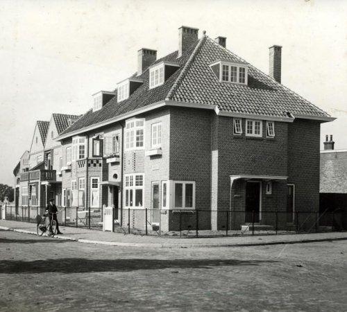 Nieuwe woningen in Schiedam, drie onder èèn kap. Hoekwoning heeft voordeur aan de zijkant. Voor het huis staat een man met fiets. Nederland, Schiedam, 1916.