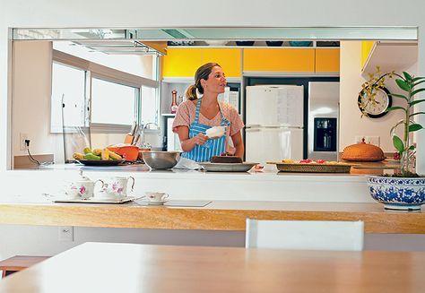 Visto da sala de jantar, o passa-prato desta casa, assinada pelos arquitetos Marcos Toledo e Maria Vianna, tem portas de madeira, que deslizam sobre o trilho metálico. A bancada de granito ajuda a apoiar os alimentos