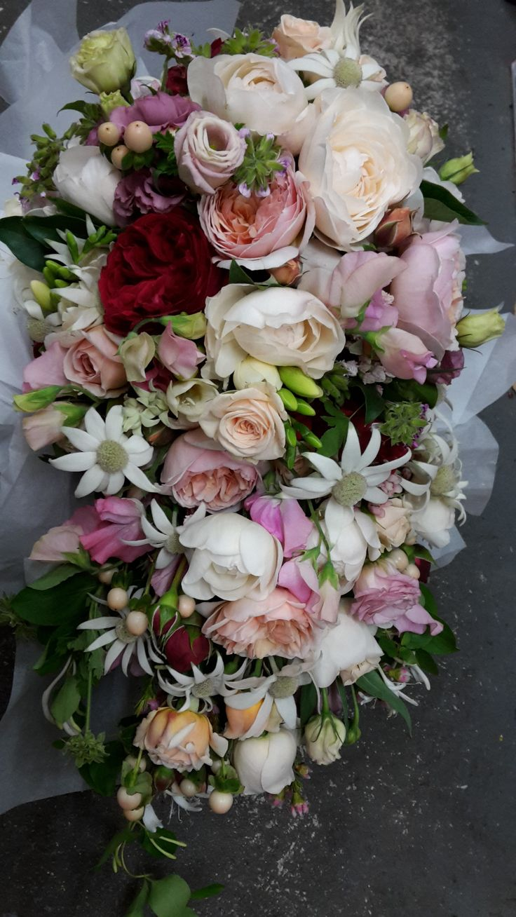 Cascade of roses, freesias, flannel flower, berries and herbs.